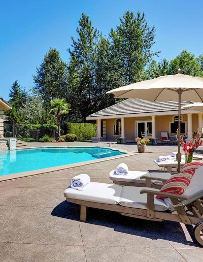 FiberBuilt Terrace Umbrellas Great backyard with swimming pool and lounge chairs in American Suburban luxury house. Northwest USA